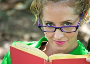 Woman in green shirt reading a book