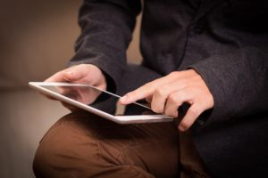 man tapping on tablet