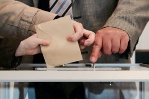 Hands putting a ballot into a voting box